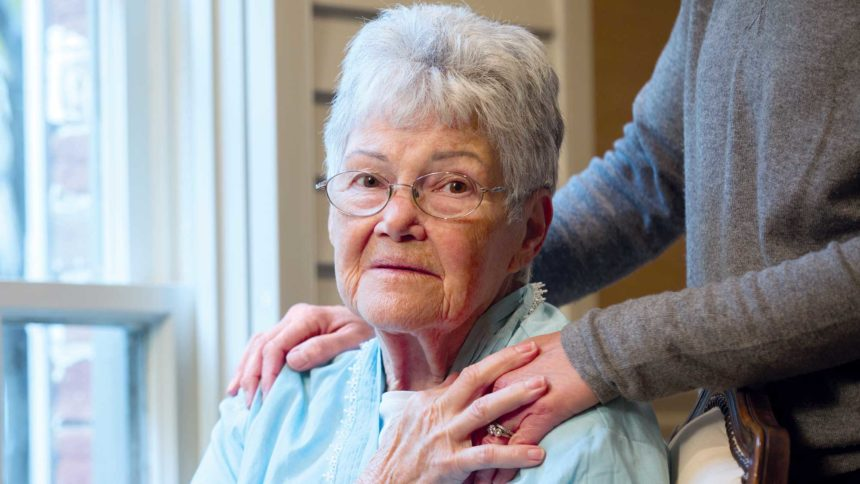 Frail, elderly women sitting, with relative's comforting hands on her shoulders
