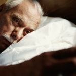Image of man in bed with head on pillow, looking at alarm clock