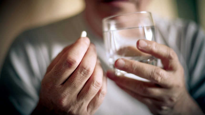 Closeup of man getting ready to take a pill with water
