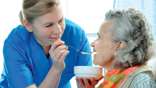 Caregiver feeding senior with dementia