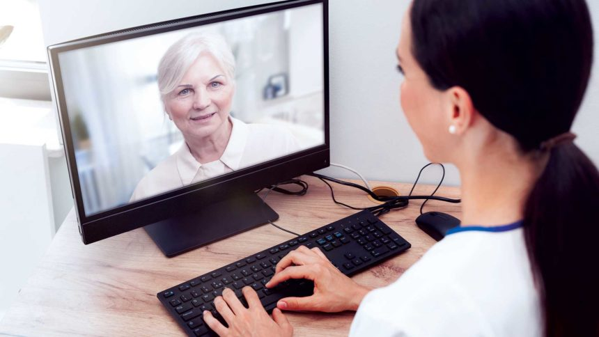 Image of clinician speaking remotely with older adult patient via a desktop computer