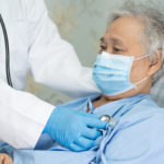 Sick elderly person wearing surgical face mask and being cared for by a clinician with stethoscope