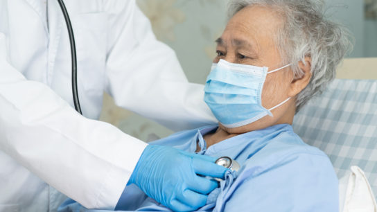 Sick elderly person with face mask being cared for by a clinician