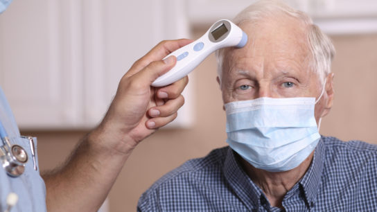 Healthcare worker checks fever of patient with infrared thermometer. Both wear protective face masks.
