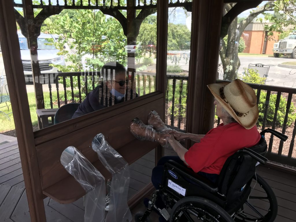 'A touching move': Family visitation booth allows residents, family members to safely make contact