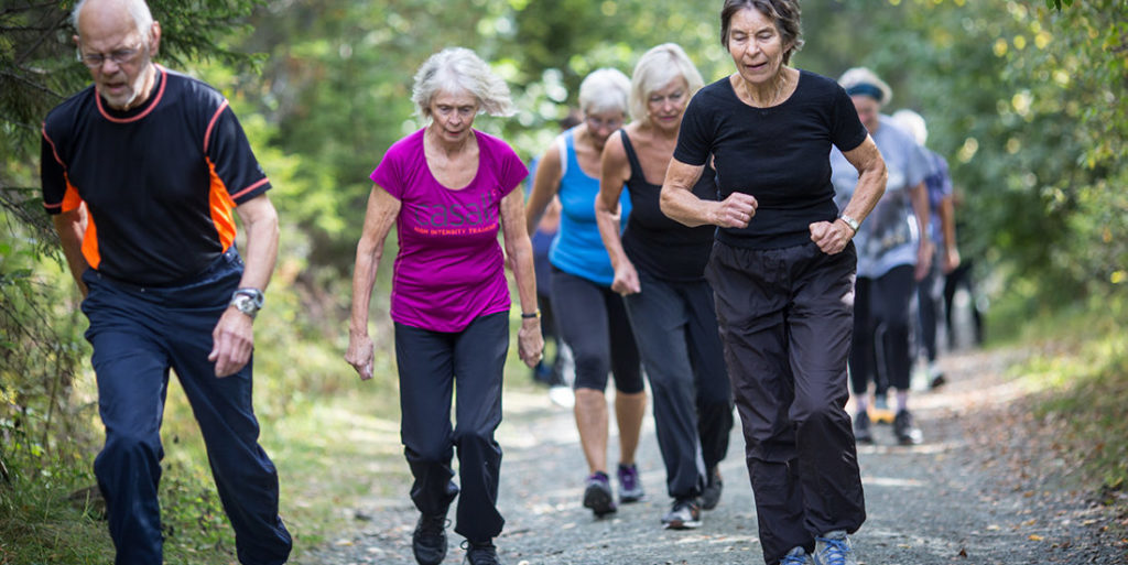 Older adults running and walking in a group in exercise gear on a wooded path.