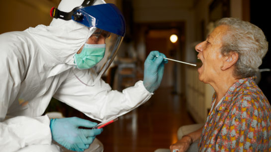 COVID test being performed on a senior woman. Care provider is wearing full PPE.