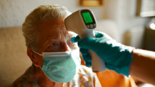 Closeup image of senior woman getting temperature check with an infrared thermometer; Credit: GettyImages-1256717963.jpg